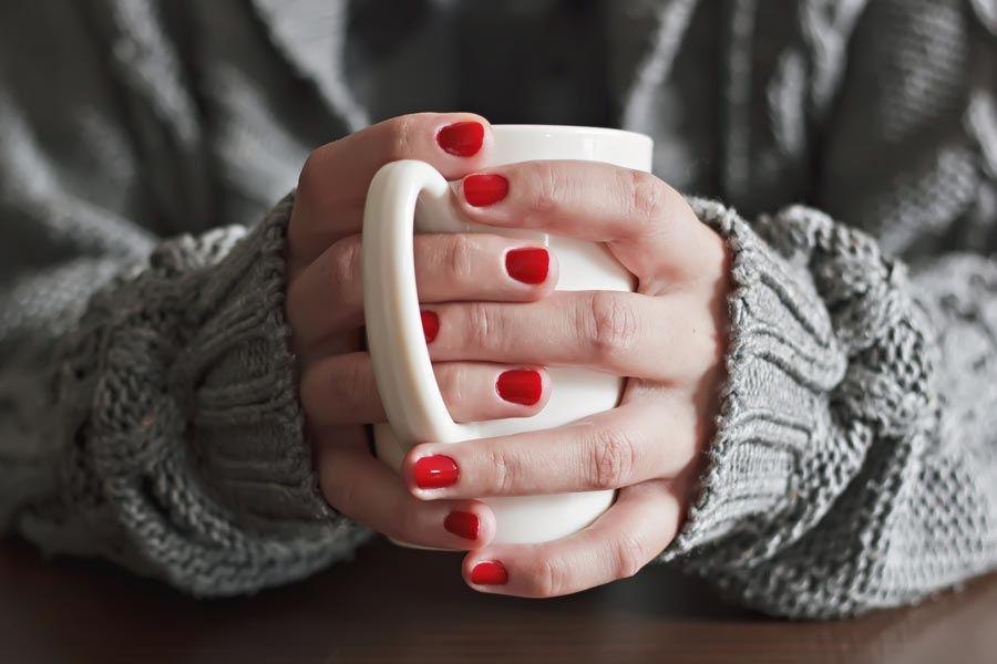 warming hands with a warm cup of coffee